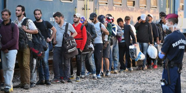MAGYARBOLY, HUNGARY - SEPTEMBER 22:  Migrants board a train at Magyarboly station heading for Austria on September 22, 2015,