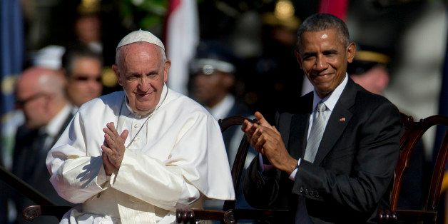 Pope Francis, left, and U.S. President Barack Obama clap after listening to a choir during an arrival ceremony on the South L