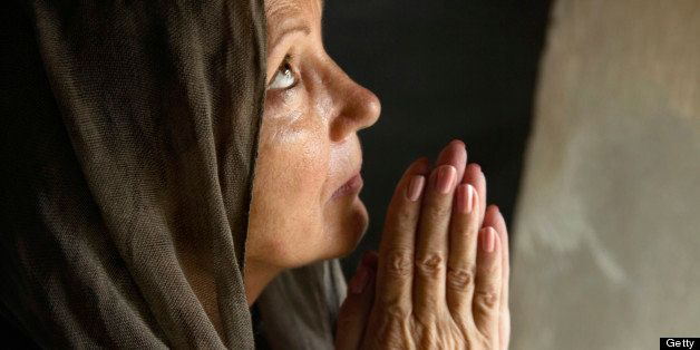 Praying mature woman folding hands in old church