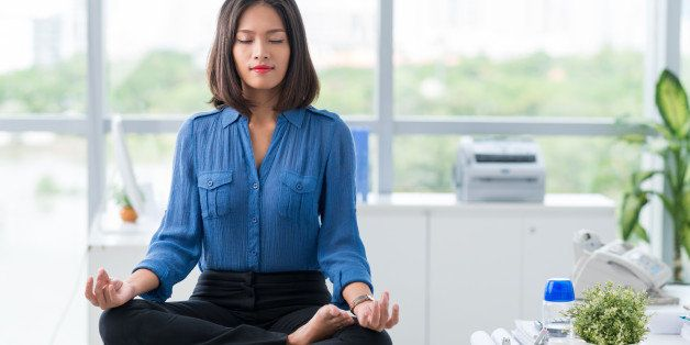 Asian businesswoman sitting on table and meditating