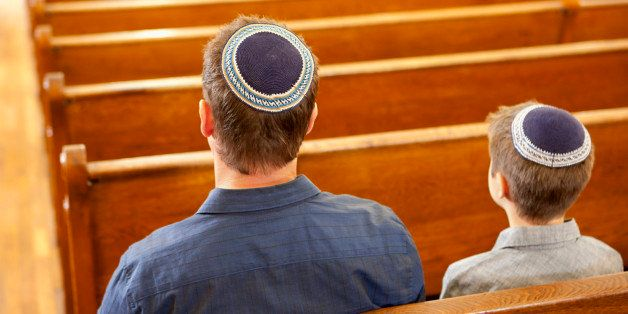 Father and son in yarmulkes sitting in synagogue