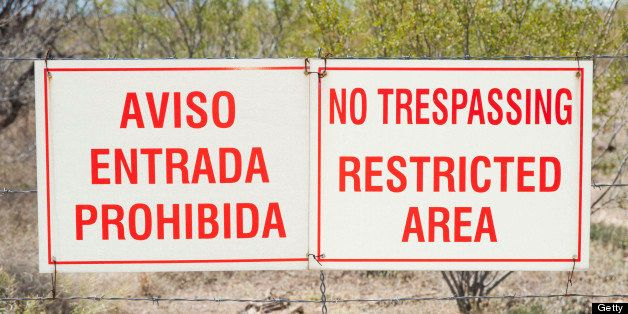 No Trespassing signs in both English and Spanish hang from a fence on the outskirts of Tucson, Arizona where illigal immigran