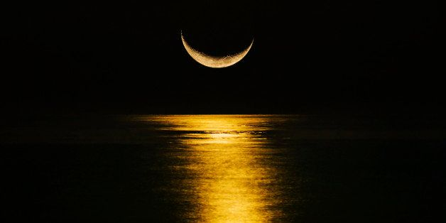 Crescent moon reflecting in sea