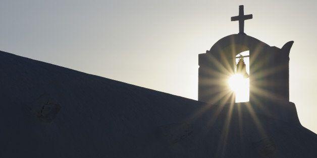 Greece, Sun shines through belltower in Oia village at Santorini