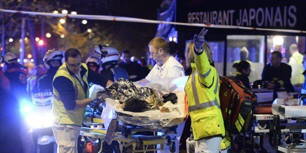 Rescuers evacuate an injured person near the Bataclan concert hall in central Paris, early on November 14, 2015. At least 120