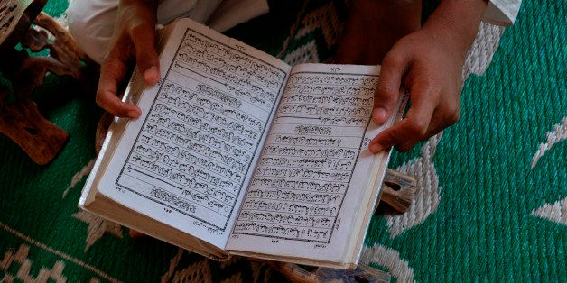Student reading the Koran in an Islamic school, New Delhi, India