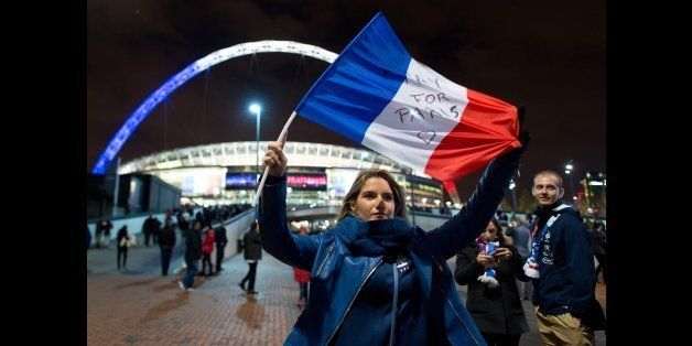 LONDON, ENGLAND - NOVEMBER 17:  A french fan waves a french flag as she arrives ahead of tonight's International friendly mat