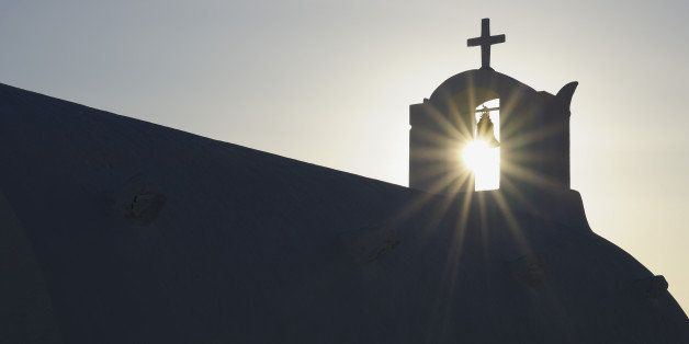 Greece, Sun shines through belltower in Oia village at Santorini