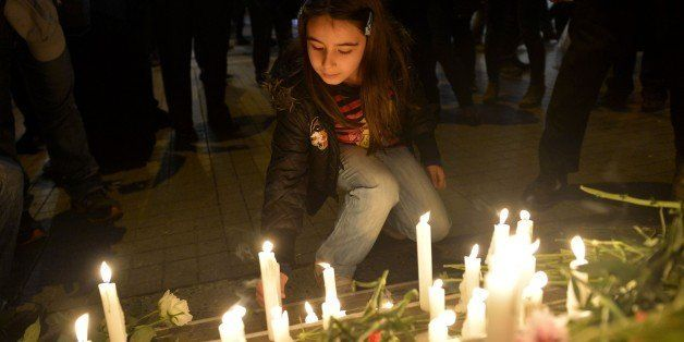 ISTANBUL, TURKEY - NOVEMBER 14: Turkish people leave flowers and candles in front of French embassy in Istanbul, Turkey to ex