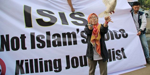 A Muslim woman releases a dove as a symbol of peace during a rally against the Islamic State group, in Jakarta, Indonesia, Fr