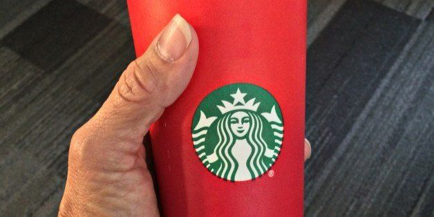 This November 9, 2015 photo shows a consumer holding the 2015 Starbucks holiday cup in Washington, DC. The unadorned red cup