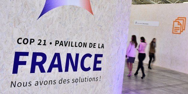 People walk by a poster hanging outside of the France pavilion reading 'We have solutions !' during the United Nations confer