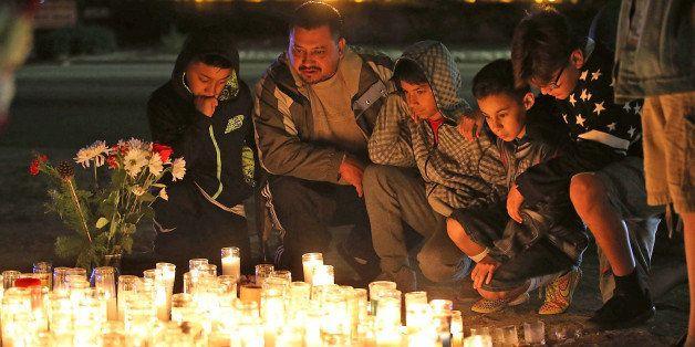 SAN BERNARDINO, CA - DECEMBER 04:  Mourners visit a makeshift memorial near the Inland Regional Center on December 4, 2015 in