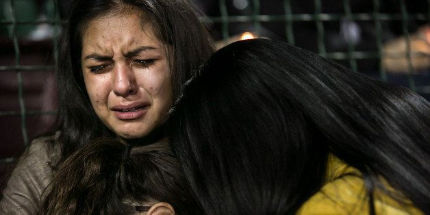 SAN BERNARDINO, CA - DECEMBER 3:  Faith Rodriguez, 15, embrace family members during an emotional candlelight vigil to honor