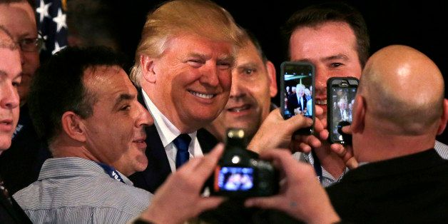 Republican presidential candidate, businessman Donald Trump smiles as he has his photograph taken with supporters after being