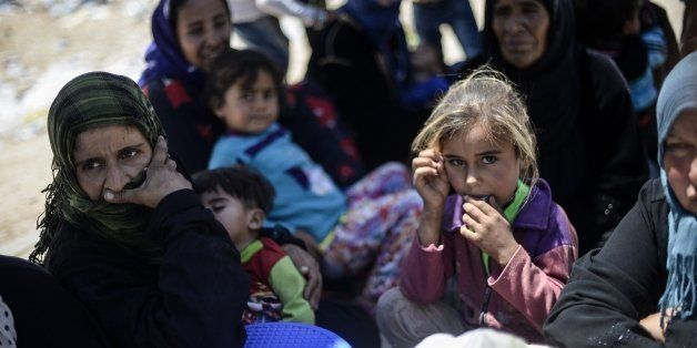 Syrian refugees sit on the side of a road that leads to the Akcakale border gate as they wait to return to their home in the