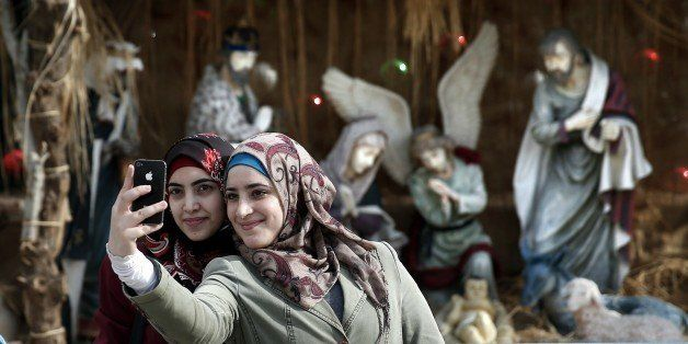 Muslim women take a selfie in front of the giant Christian manger displayed on the Manger Square in front of the Church of th