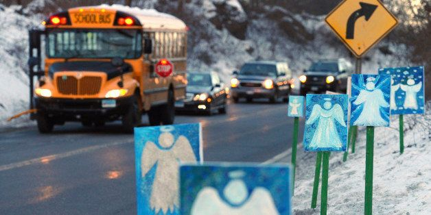FILE - In this Jan. 3, 2013, file photo, a bus traveling from Newtown, Conn., to Monroe stops near 26 angel signs posted alon