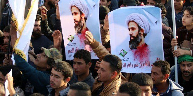 Supporters of Iraqi Shiite cleric Moqtada al-Sadr hold posters of prominent Shiite cleric Nimr al-Nimr during a demonstration