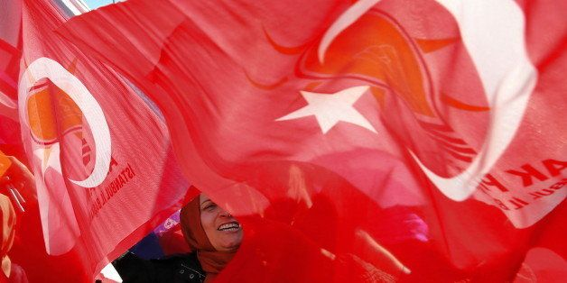 A supporter of Turkish Prime Minister and leader of the Justice and Development Party (AKP), Ahmet Davutoglu, waves her natio