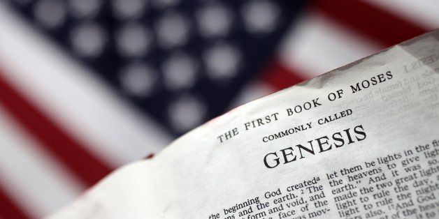 'XXXL photo of a bible open to the first page of Genesis with selective focus in the foreground and a blurred American flag i