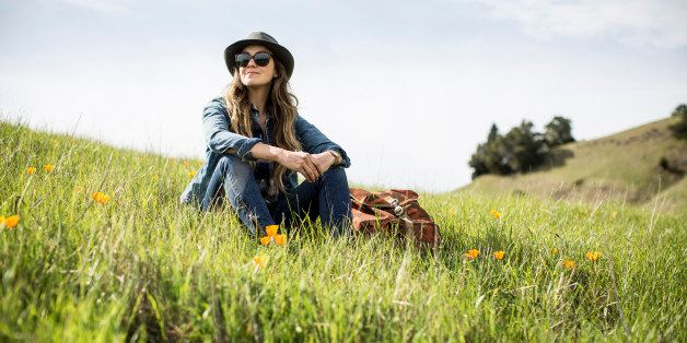 A woman with a backpack and hat sitting in a green grassy field.