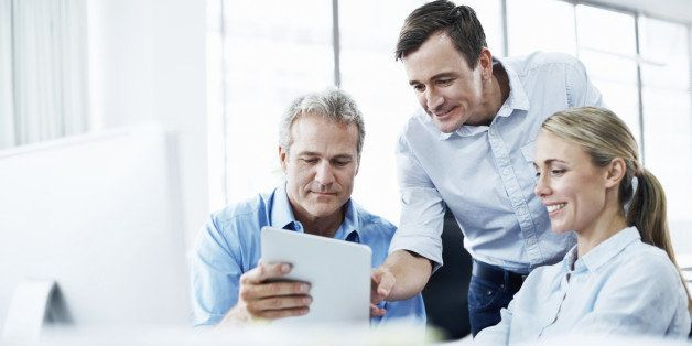 Three businesspeople looking at a digital tablet while working together in their office