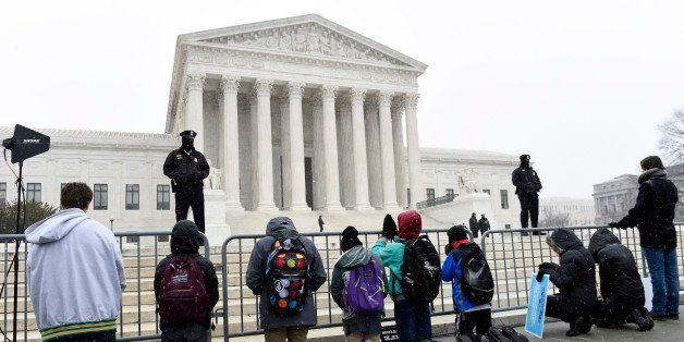 People kneel outside the Supreme Court in Washington, Friday, Jan. 22, 2016, during the March for Life 2016, the annual rally