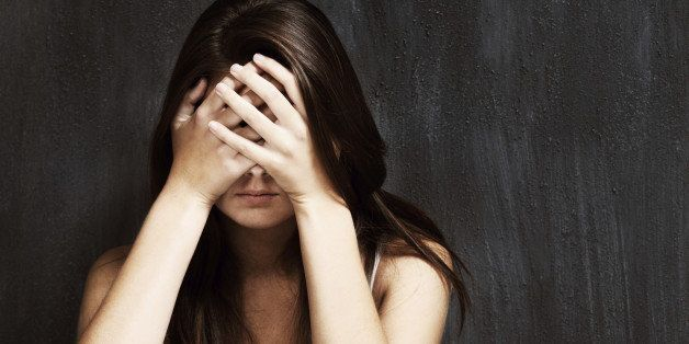 A studio shot of a sad young woman holding her head in her hands