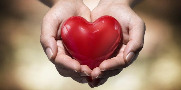 heart in heart hands- warm background