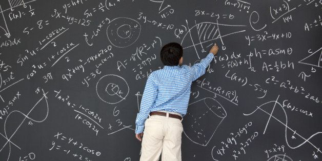 Ten year old boy at chalkboard full of trigonometry, algebra, and calculus problems.