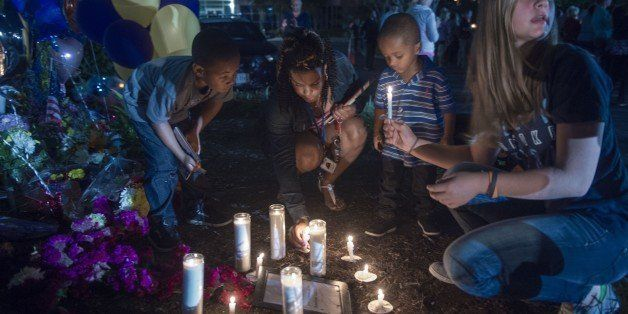 People in Roanoke participate in a candlelight vigil placing their candles near the memorial shrine of balloons and flowers o