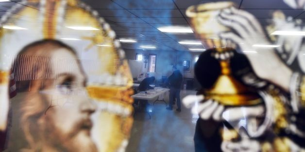 A local resident is reflected on a religious picture as he votes for the first US presidential primary at a church in Concord