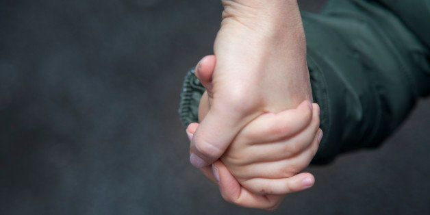 Child holding mother's hand.