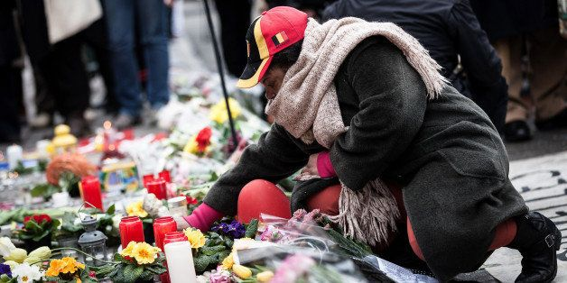 A woman lights a candle at a memorial for victims of attacks in Brussels on Wednesday, March 23, 2016. Belgian authorities we