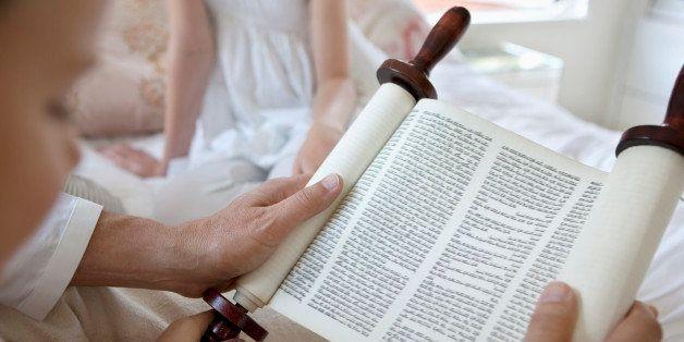 Family reading Torah scrolls together
