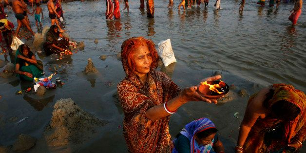 Indian women offer prayers at the 'Sangam', confluence of rivers Ganges, Yamuna, and mythical Saraswati, on the auspicious oc