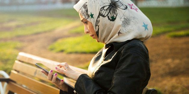Woman reading on tablet in a city park. Istanbul, Turkey.