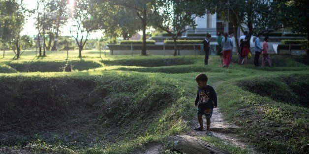 This photo taken on November 5, 2014 shows a child looking at the site of mass graves for victims of the Khmer Rouge at the C