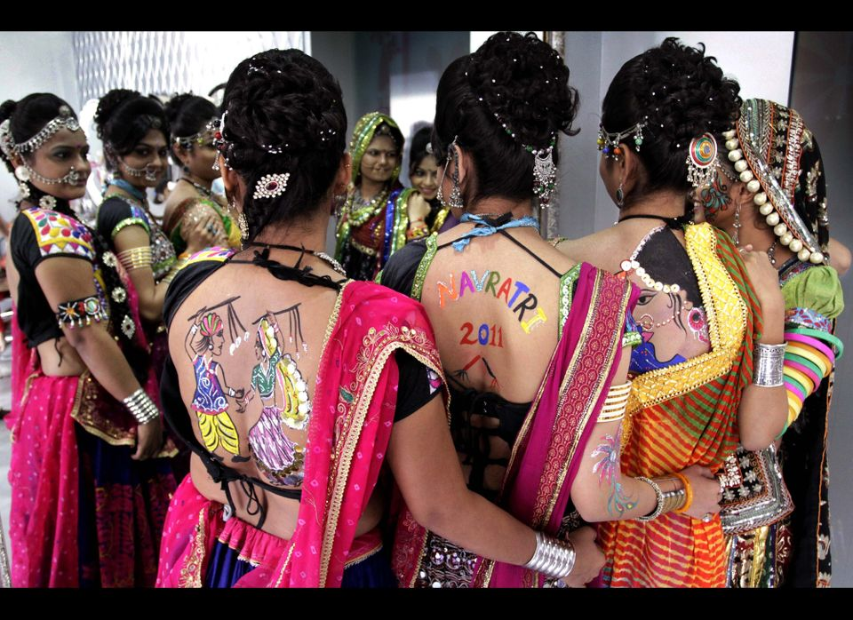 Indian women with their back painted and wearing traditional attire pose for photograph as they get ready for a practice of G