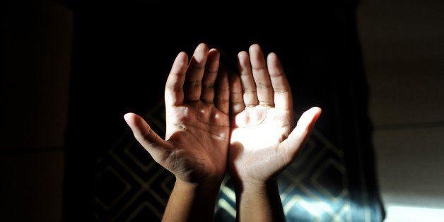 A muslim woman making dua(prayers) as light falls on her palm.
