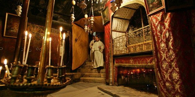 Catholic priests walk inside the Grotto, believed by Christians to be the birth place of Jesus, at the Church of the Nativity