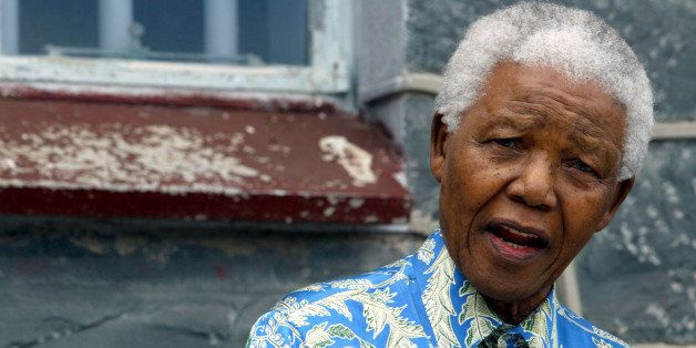 Nelson Mandela speaks to musicians beneath the window of his prison cell on Robben Island near Cape Town, November 28, 2003.