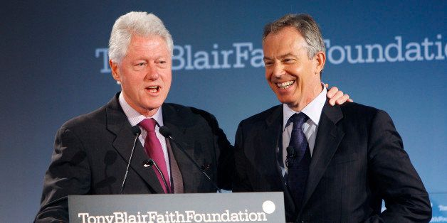 Former U.S. president Bill Clinton (L) introduces former British Prime Minister Tony Blair to the podium at the official  lau
