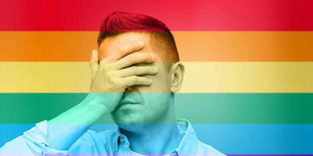homosexual, homophobia, intolerance and people concept - unhappy gay man covering his eyes by hand over rainbow flag backgrou