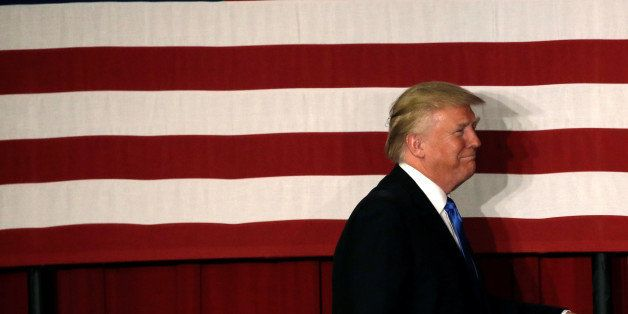 U.S. Republican presidential candidate Donald walks to the stage past an American flag at a fundraising event where he appear