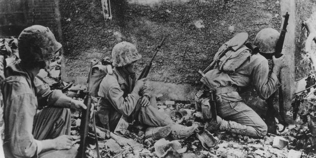 8th June 1945:  A group of 6th Division Marines take cover behind a wall during their fight amid the wrecked homes and rubble