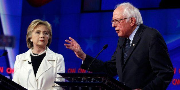 Democratic U.S. presidential candidate Hillary Clinton (L) listens to Senator Bernie Sanders speak during a Democratic debate