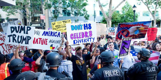 Police form a line to contain protesters outside a campaign rally for Republican presidential candidate Donald Trump on Thurs