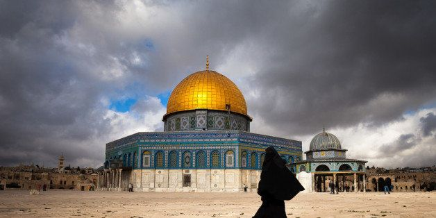 Muslim woman in a black burqa walking by the Dome of the Rock in Jerusalem.The Dome of the Rock is a shrine located on the Te